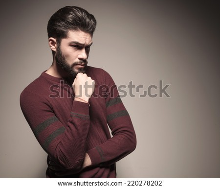 Side view of a fashionable man in burgundy sweater holding his hand to the chin, looking away from the camera - stock photo
