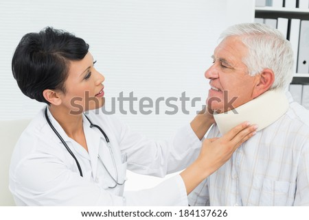 Side view of a female doctor examining a senior patients neck at medical office - stock photo