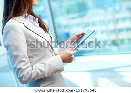 Side-view of a female office worker holding a digital tablet - stock photo
