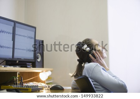 Side view of a female sound engineer listening to music - stock photo