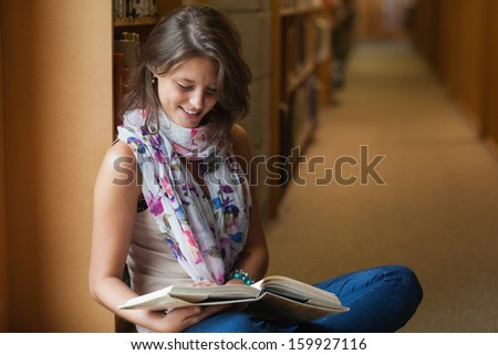 Side view of a female student sitting and reading a book in the library aisle - stock photo