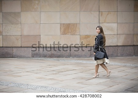 Side view of a Filipino Businesswoman walking on city street in front of modern marble wall.