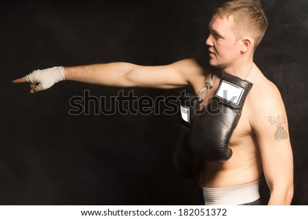 Side view of a fit young boxer standing pointing with his bandaged hand in the darkness with his gloves hanging around his neck - stock photo