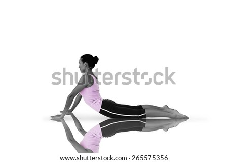 Side view of a fit young woman doing the cobra pose against mirror - stock photo
