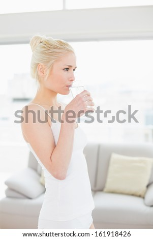 Side view of a fit young woman drinking water at the gym after working out  - stock photo