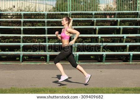 Side view of a fit young woman jogging at the stadium  - stock photo