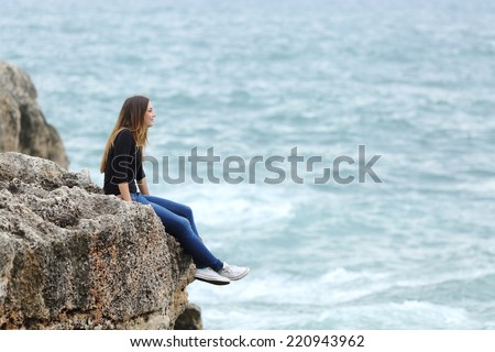 Side view of a full body of a casual woman thinking sitting in a cliff watching the sea - stock photo