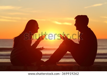 Side view of a full body of two friends or couple silhouette of teens sitting and talking at sunrise on the beach with the sun in the middle - stock photo