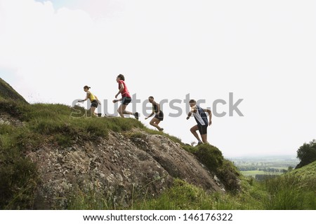 Side view of a group of people running on hill - stock photo