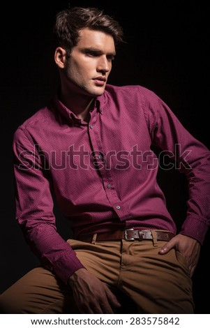 Side view of a handsome casual man sitting while looking away. - stock photo