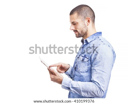 Side view of a handsome casual man using a digital tablet, isolated on white background