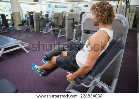 Side view of a handsome young man doing leg workout at the gym
