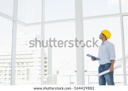 Side view of a handyman in yellow hard hat with clipboard and blueprint looking up at window in a bright office - stock photo