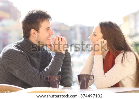 Side view of a happy couple dating and flirting in love looking each other in a bar terrace with a port of urbanization in the background - stock photo