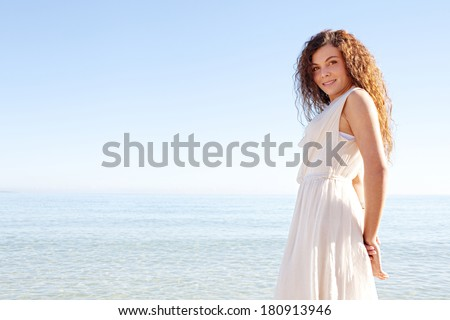 Side view of a healthy and beautiful young woman relaxing on a beach during a sunny summer day on holiday, standing against a bright blue sky and smiling. Outdoors beauty lifestyle.