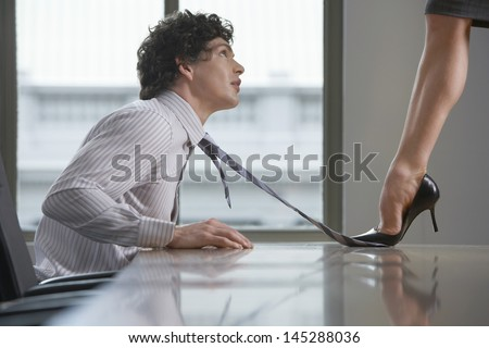 Side view of a highheeld businesswoman stepping on businessman's tie on desk - stock photo