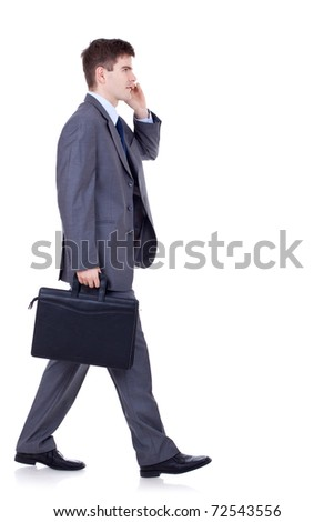 side view of a hurrying business man talking on the mobile phone