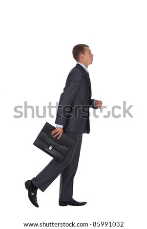 side view of a hurrying business man with briefcase in hand over white background - stock photo