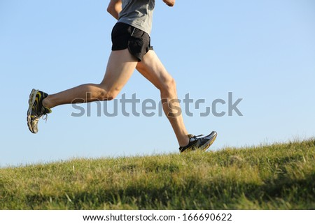 Side view of a jogger legs running on the grass with the horizon in the background - stock photo