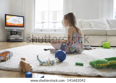 Side view of a little girl watching television with toys on floor - stock photo