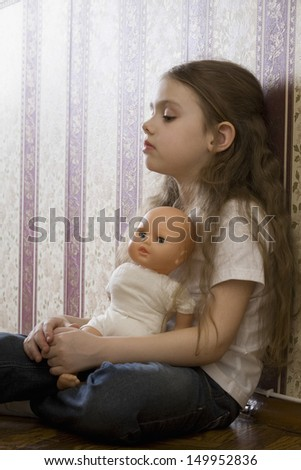 Side view of a little girl with doll sitting at home - stock photo