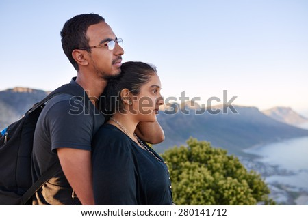 Side view of a loving young Indian couple standing closely together while on a nature hike and looking into the distance  - stock photo