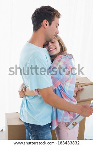 Side view of a loving young woman embracing man at home