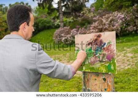 Side view of a male artist painting with oils and acrylics finishing touches working  on a trestle and easel  during an art class in a park - stock photo