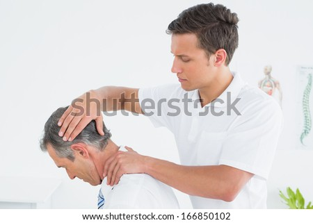 Side view of a male chiropractor doing neck adjustment - stock photo