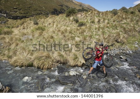Side view of a male cyclist carrying bike in countryside river - stock photo