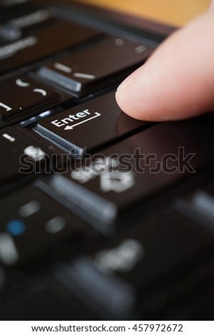 Side view of a male finger pressing black key with a caption Enter on the computer keyboard  - stock photo