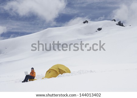 Side view of a male hiker using laptop by tent on snowy mountain slope - stock photo
