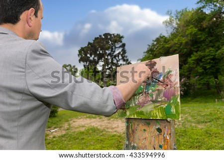 Side view of a male middle-aged contemplative artist working  on a trestle painting with oils and acrylics during an art class in a forest - stock photo