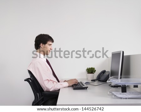 Side view of a male office worker using computer at desk in the office - stock photo