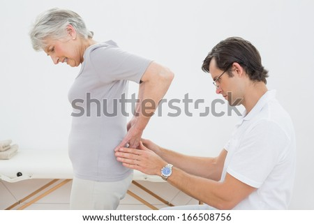 Side view of a male physiotherapist examining senior woman's back in the medical office - stock photo