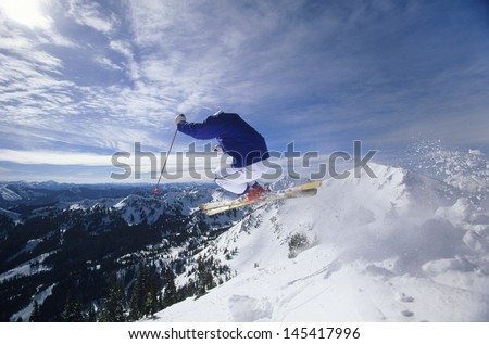 Side view of a male skier jumping on mountain top hitting the slopes