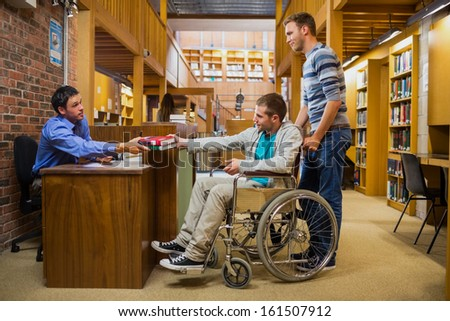 Side view of a male student in wheelchair at the counter in college library - stock photo
