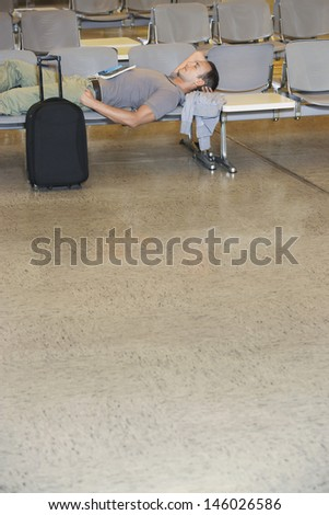 Side view of a male traveler lying on chairs in airport lobby - stock photo