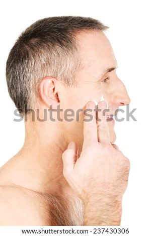 Side view of a man applying cream on his face. - stock photo