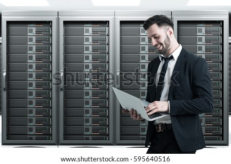 Side view of a man holding his laptop while standing in a server room with four large servers. Concept of IT work.