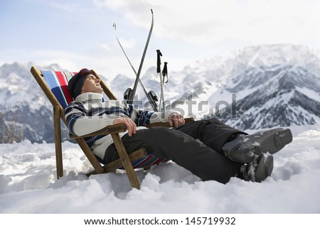 Side view of a man in warm clothing resting on deckchair in snowy mountains - stock photo