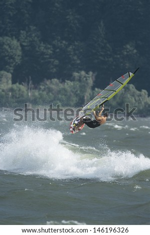 Side view of a man jumping whilst windsurfing - stock photo