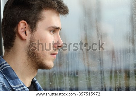 Side view of a man longing and looking through window in a sad rainy day - stock photo