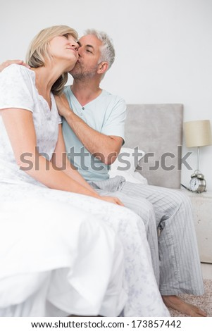 Side view of a mature man kissing womans cheek in bed at the home