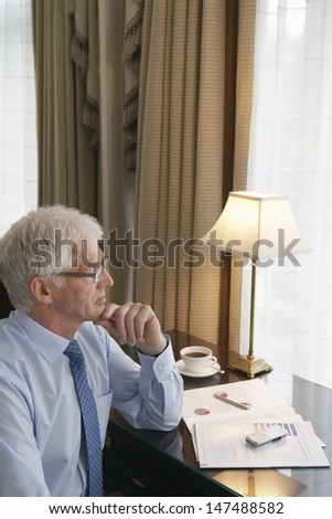 Side view of a middle aged businessman with hand on chin sitting at desk - stock photo
