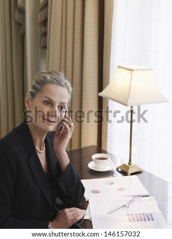 Side view of a middle aged businesswoman on call at home desk - stock photo