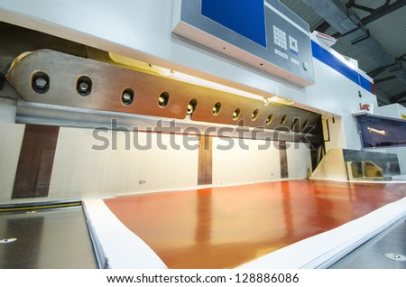 side view of a modern paper guillotine with touch screen used in commercial printing industry (industrial knife cutter) - stock photo