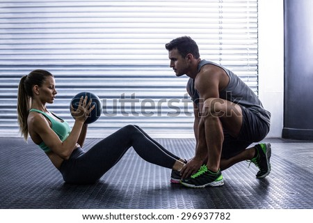 Side view of a muscular couple doing abdominal ball exercise - stock photo