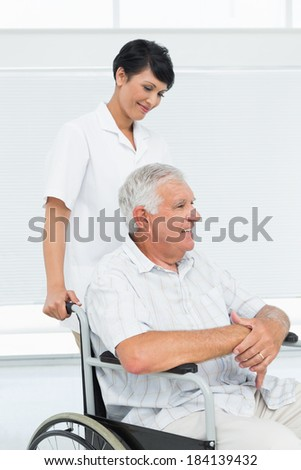 Side view of a nurse with senior patient sitting in wheelchair at the hospital