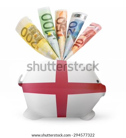 Side view of a piggy bank with the flag design of England and various european banknotes.(series) - stock photo